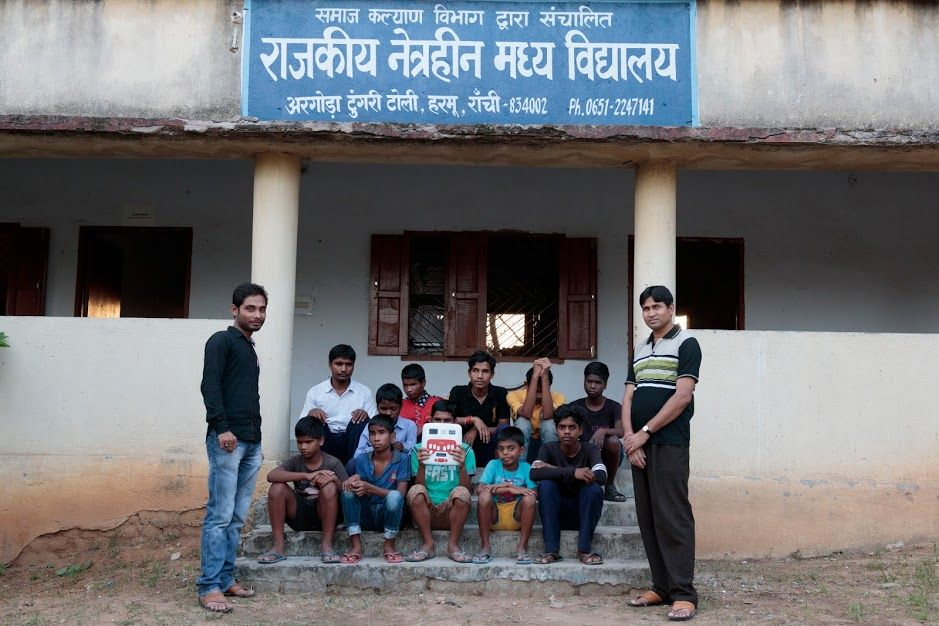 Two rows of children are seated on the stairs in front of a building. The sign on the building's roof reads Rajyakrit Netrahin Madhya Vidyalaya in Hindi. The child in the middle of the second row holds up an Annie in front of his face. Two adult men are standing on either side of the stairs