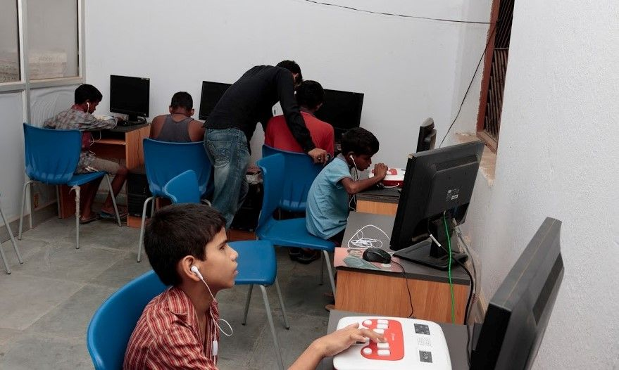 There are a row of 3 students sitting at tables with computer monitors at the far end of the room. A man in a black shirt and jeans looks over the shoulder of a boy in a red t shirt. On the right side of the room, two boys are sitting at tables with Annies and computer monitors. They have earphones plugged into their ears, to the Annies.