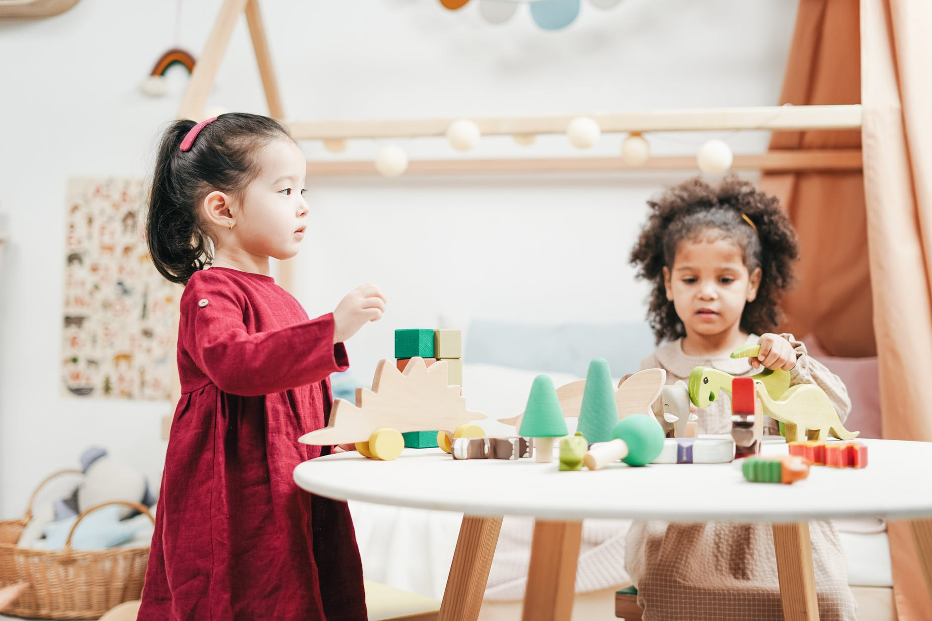 Two girls are playing with their toys. placed on a table. The toys include blocks of various colours, such as cyan, blue, and white, cones, as well as dinosaur figurines.